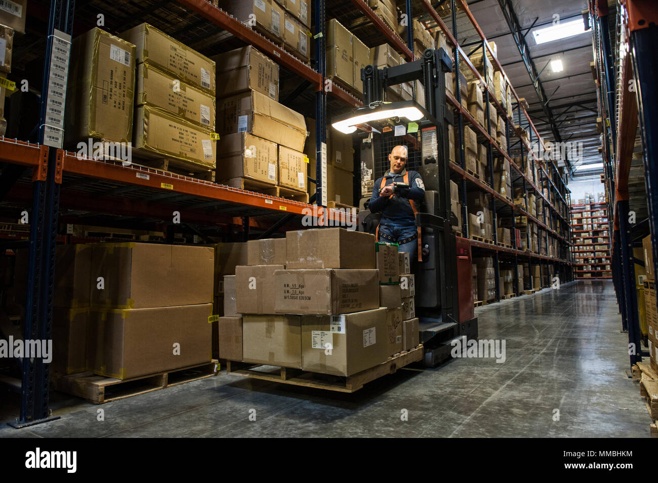 Warehouse worker wearing a safety harness while opeating a motorized stock picker in an aisle between large racks of cardboard boxes holding product o - Stock Image