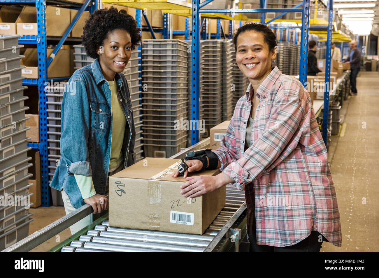 Team portrait of multi-ethnic female warehouse workers working next to a motorzied feed conveyor in a large distribution warehouse. - Stock Image