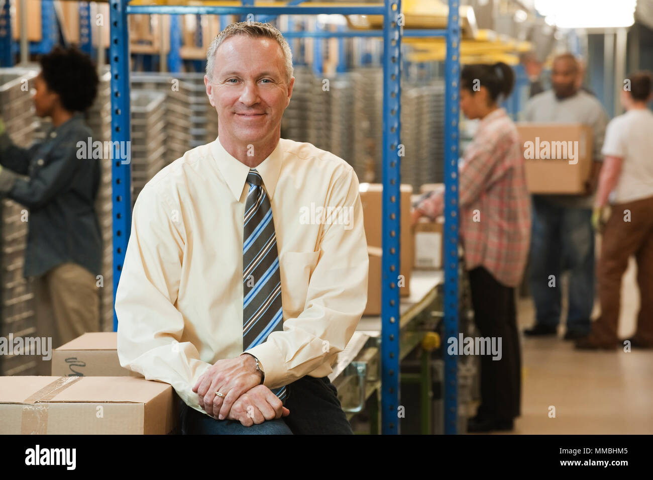 Portrait of a male caucasian executive in a dress shirt and tie  next to a motorized converyor system in a large distribution warehouse. - Stock Image