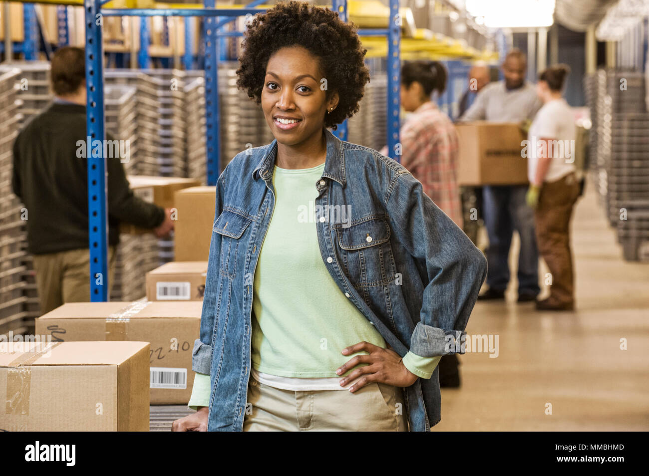 Portrait of an African American female warehouse worker in a large distribution warehouse with products stored in cardboard boxes. - Stock Image