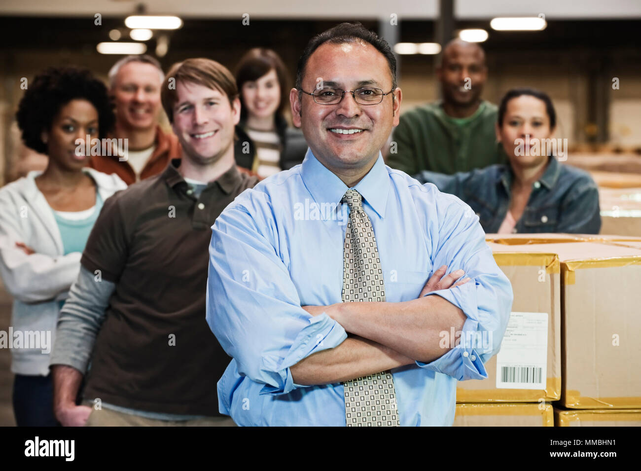 Team portrait of multi-ethnic  warehouse workers lead by a Hispanic American male executive and surrounded by large racks of products stored in cardbo - Stock Image