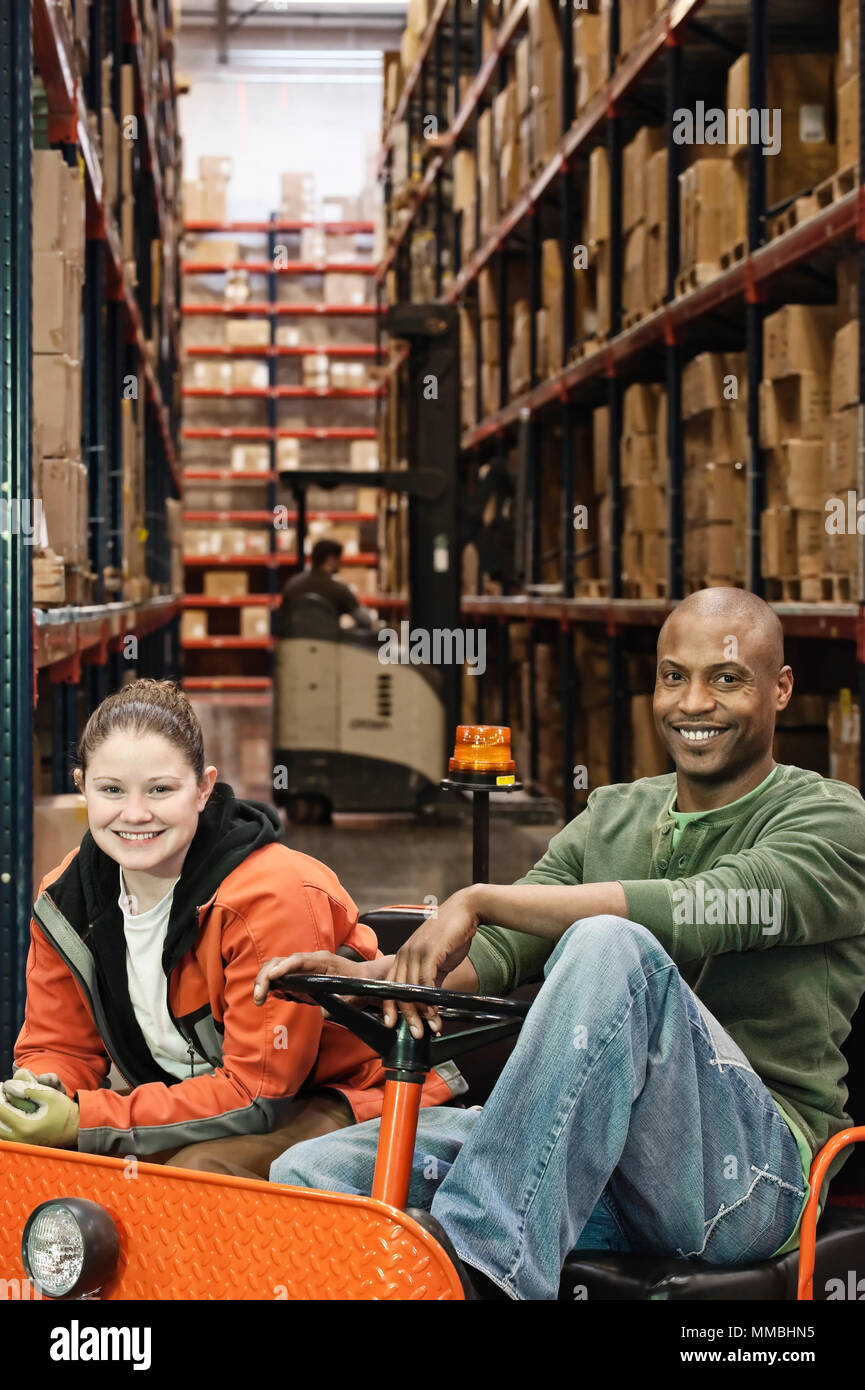 Portrait of a caucasian female warehoiuse worker and an African American warehouse worker sitting on a motorized cart in an aisle of large racks of pr - Stock Image