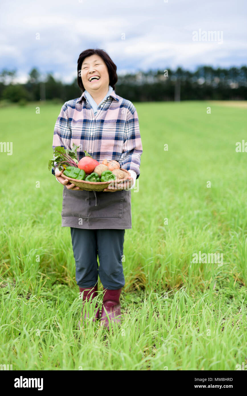 Woman with black hair wearing checkered shirt standing in a field, holding basket with fresh vegetables, smiling at camera. - Stock Image