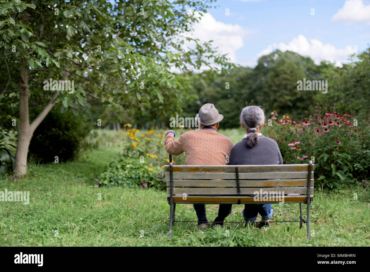 Husband and wife, rear view of elderly man wearing hat and woman sitting side by side on a bench in a garden. - Stock Image