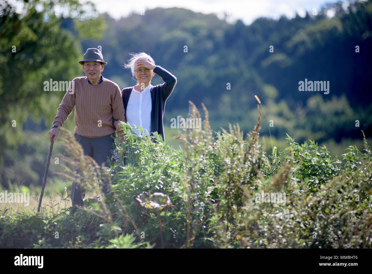 Husband and wife, elderly man wearing hat and using walking stick and elderly woman walking along path. - Stock Image