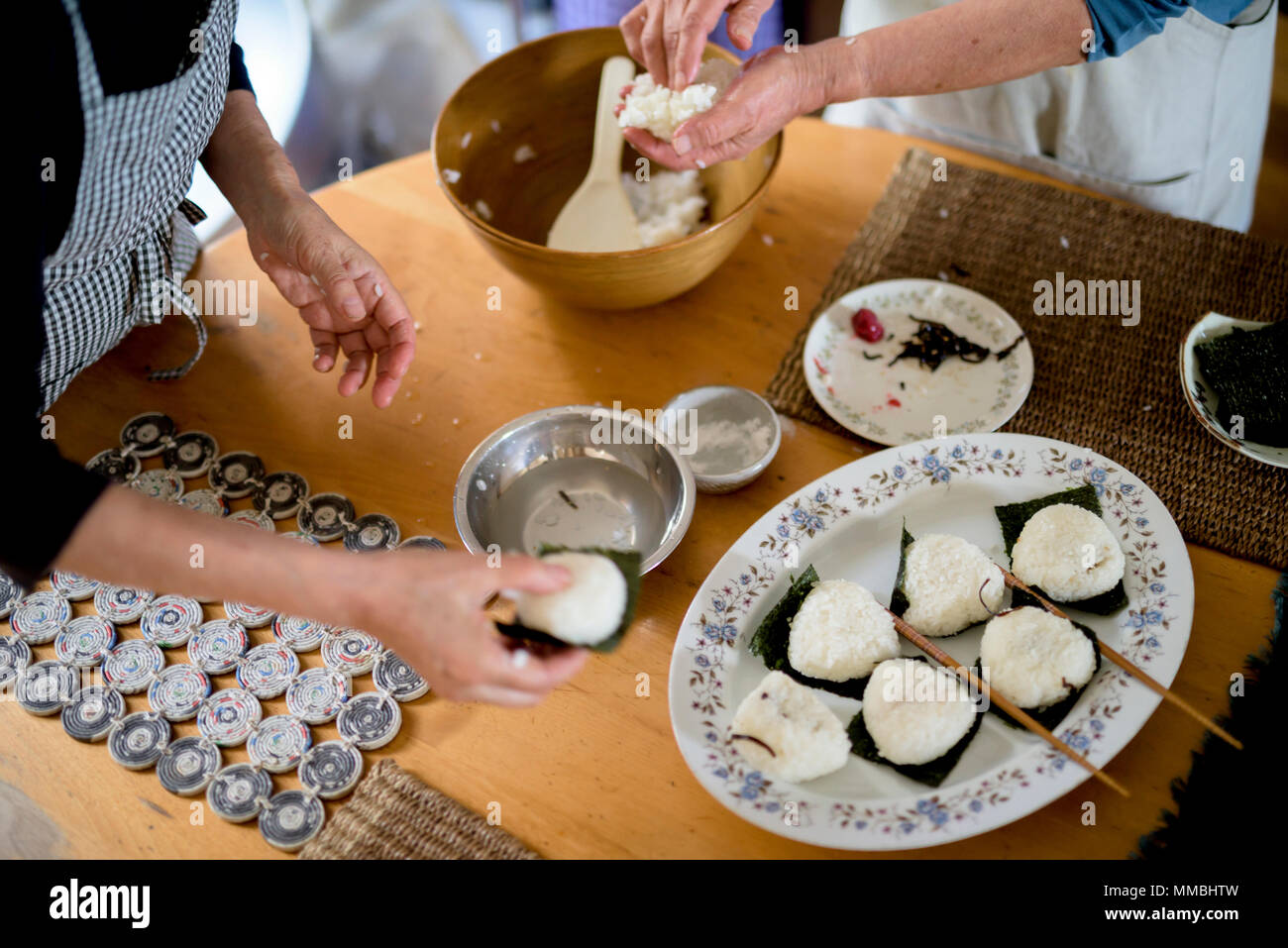 High angle close up of two women standing at a table, preparing plate of sushi. - Stock Image