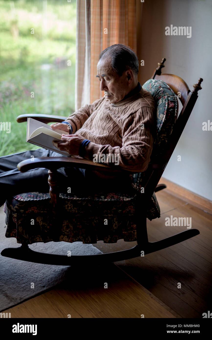 Elderly man sitting in rocking chair by a window, reading book. - Stock Image