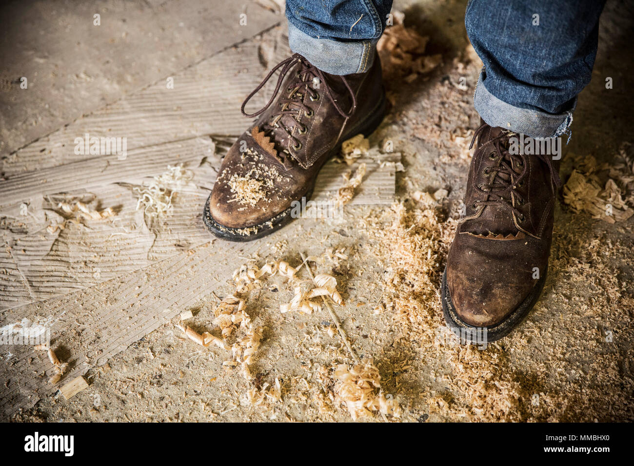 High angle view of a man wearing jeans and brown leather boots standing in a workshop, wood shavings on the floor. - Stock Image