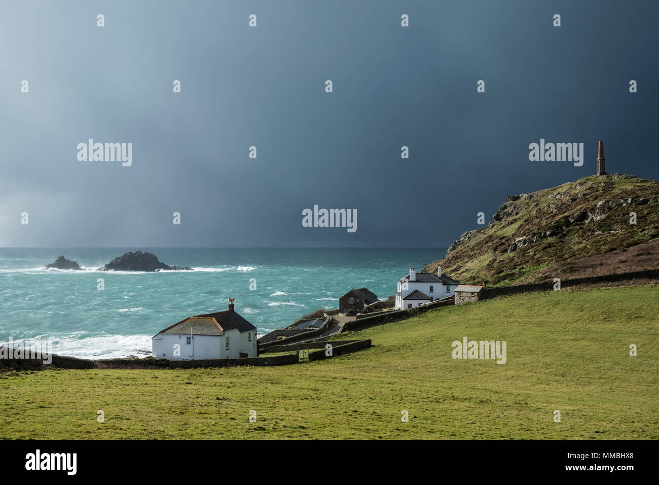 Cot Valley, St Just, West Cornwall coastline. View of cottages overlooking the coast and the Brisons Rocks under a darkening stormy sky. - Stock Image