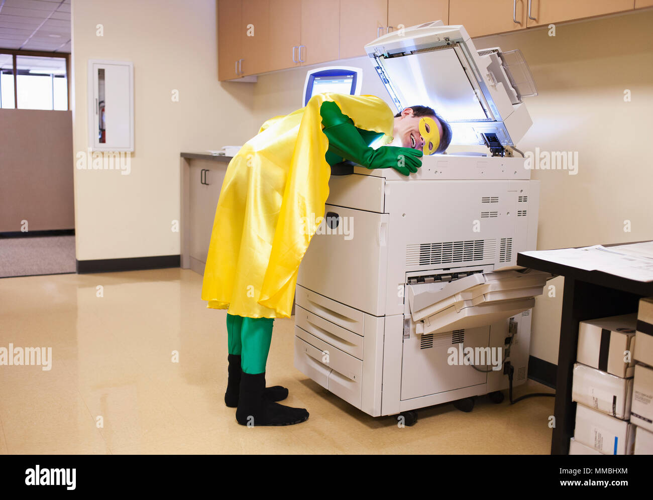 Caucasian businessman office super hero stands at photocopier, making copy of his head. - Stock Image