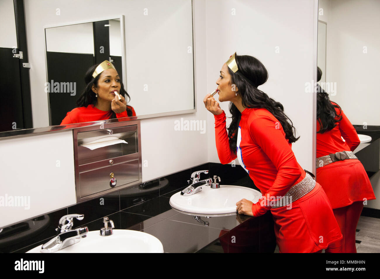 A black businesswoman office super hero takes a make up break between super hero feats. - Stock Image