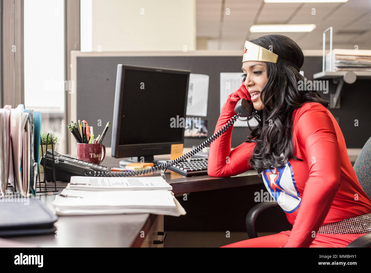 A black office superhero businesswoman takes a call in her office from a client. - Stock Image