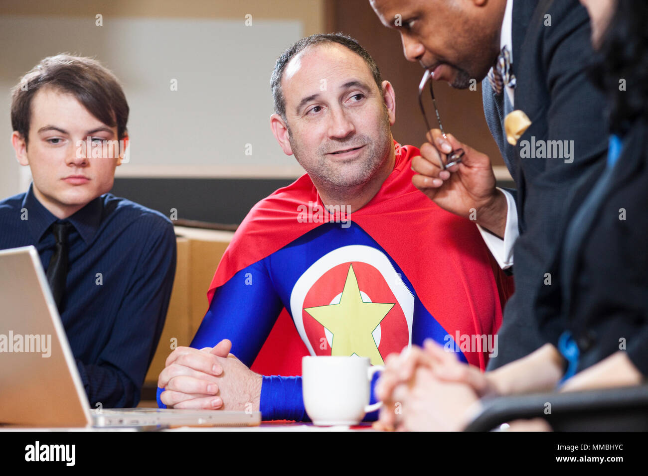 A middle aged caucasian office super hero in a meeting with his staff. - Stock Image