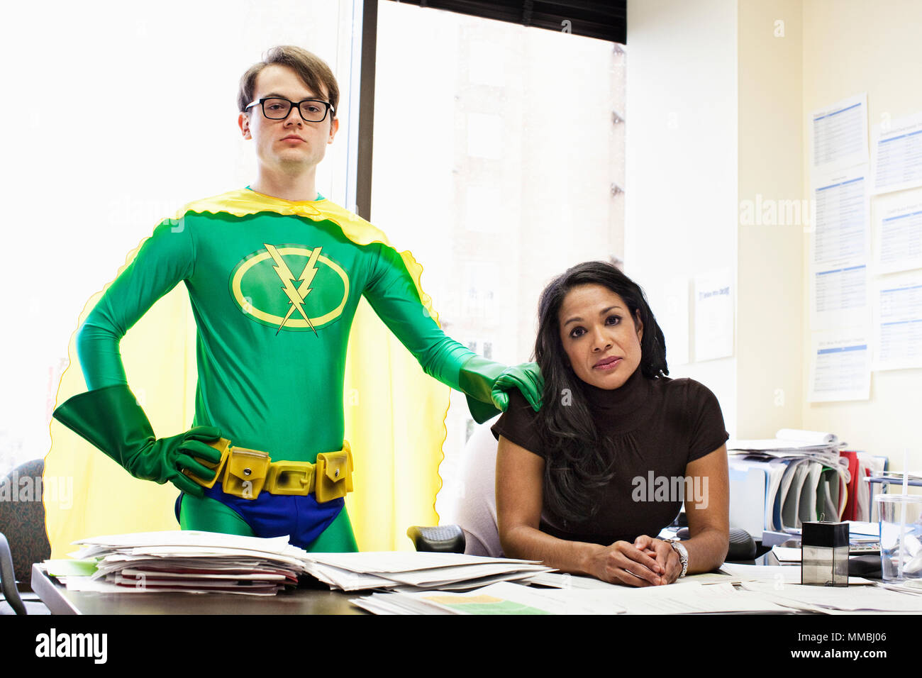 A black business woman at her desk with her caucasian office super hero advisor. - Stock Image