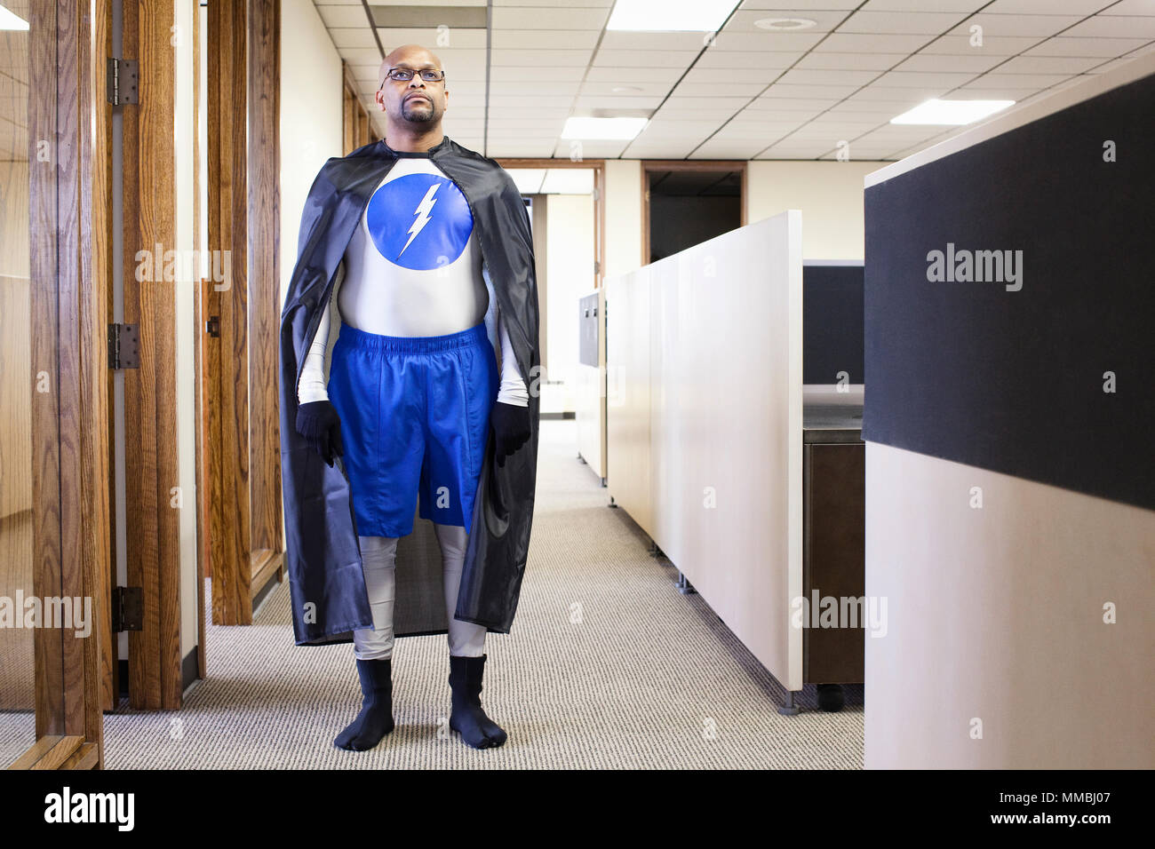 A black businessman office super hero standing in an office hallway. - Stock Image