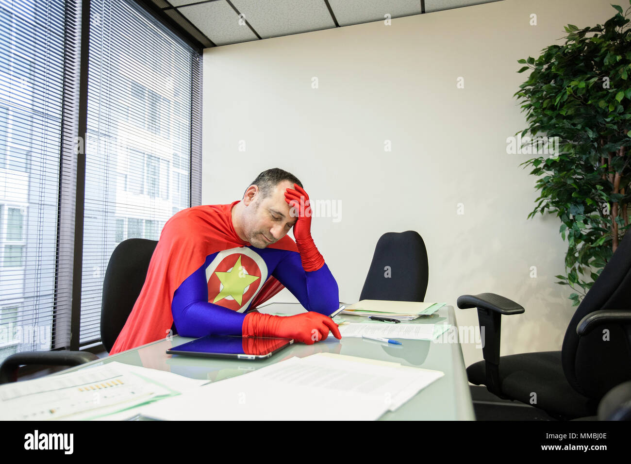 A middle aged caucasisan office super hero ponders the stress of the job. - Stock Image