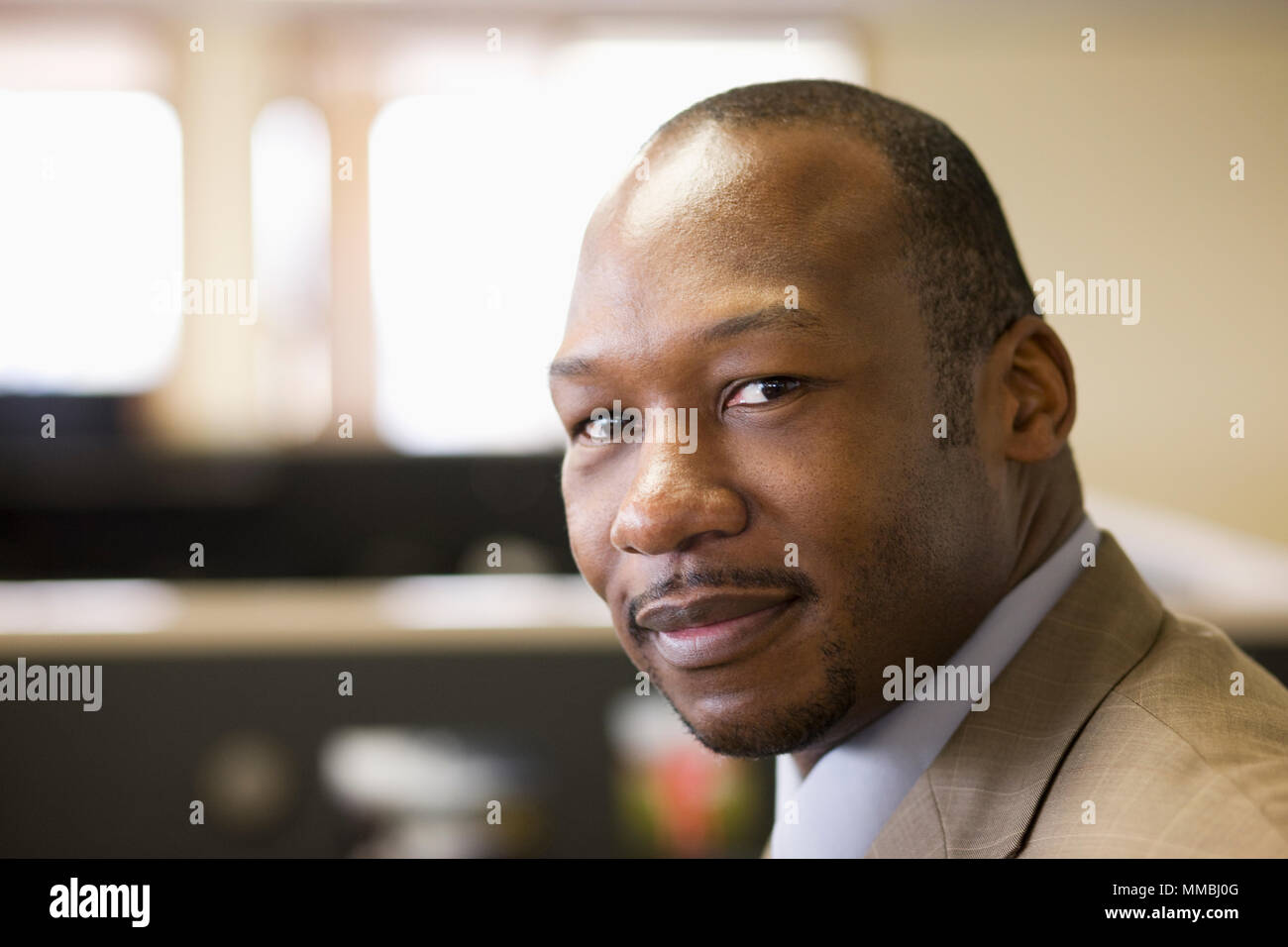 A black businessman at his desk in his office. - Stock Image