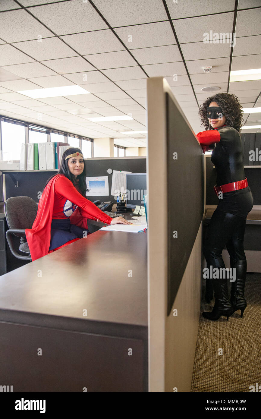 Two women office super hero's in their office. - Stock Image
