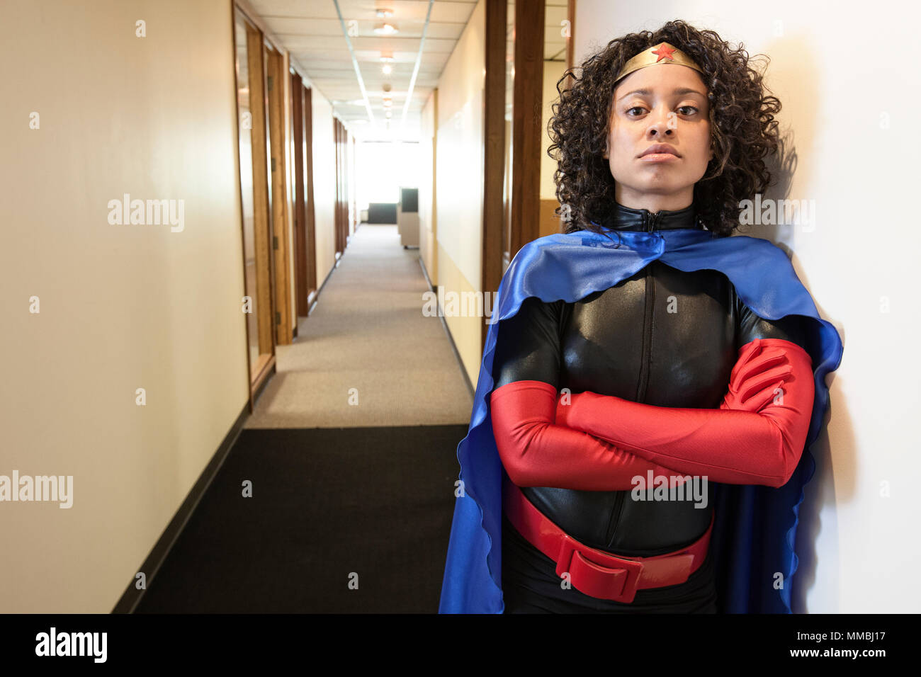A black businesswoman office super hero standing in a hallway of her office. - Stock Image