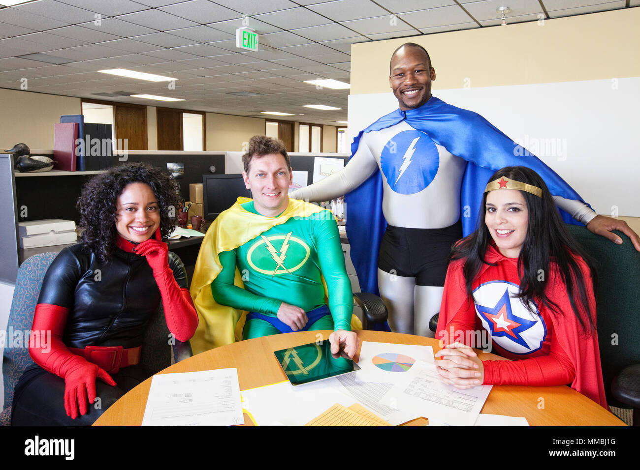 A mixed race team of office super hero's in thier office. - Stock Image