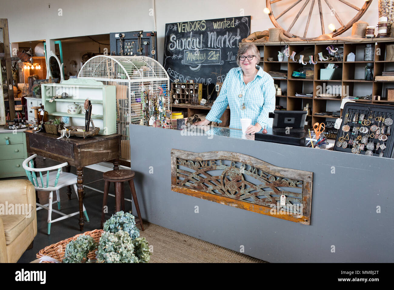 Caucasian woman owner of an antique store standing near the cash register - Stock Image