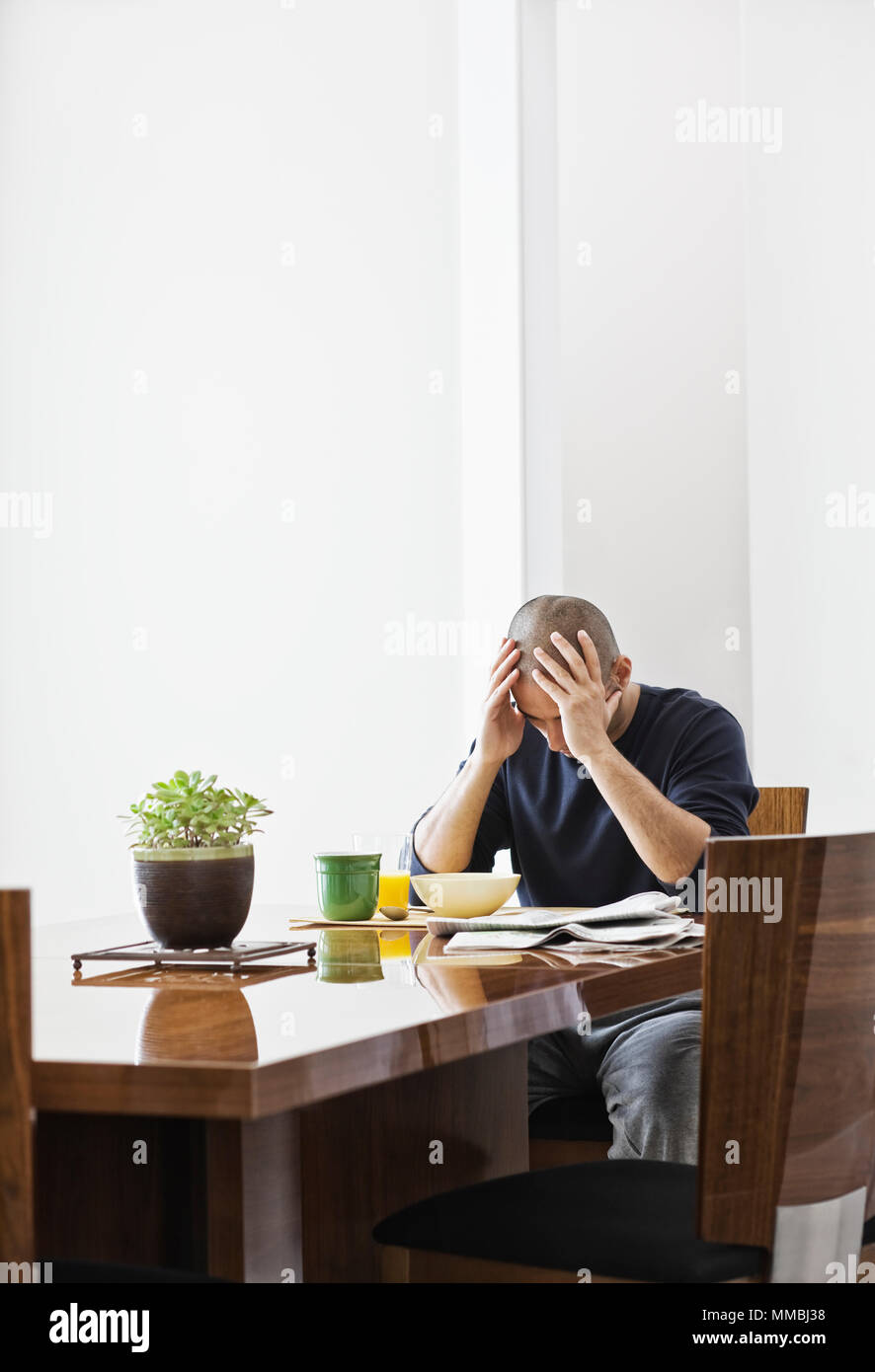 HIspanic man under stress while sitting at the dining room table in a new home. - Stock Image
