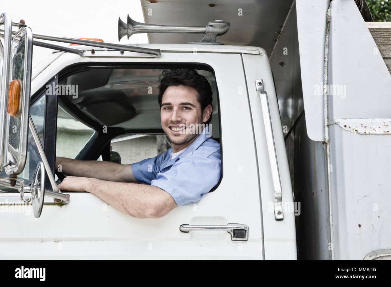 Caucasian man truck driver in company truck window. - Stock Image