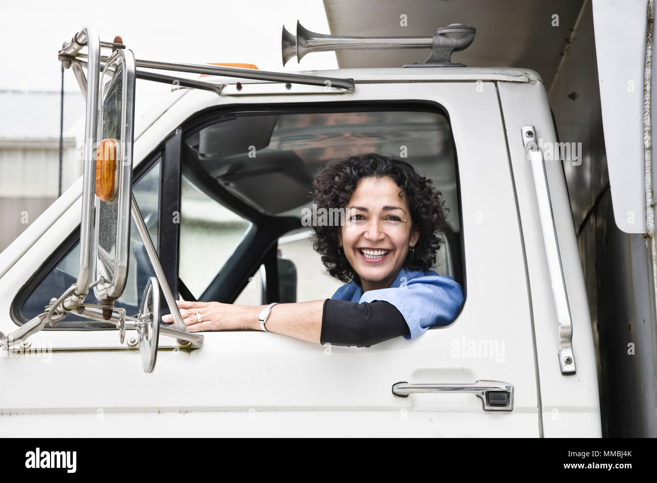 Hispanic woman truck driver and company delivery truck. - Stock Image