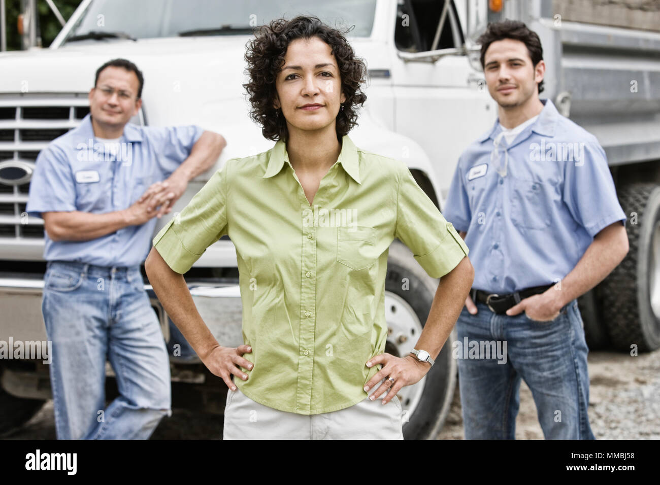 Mixed race team of workers at a landscape company with a woman in the lead. - Stock Image