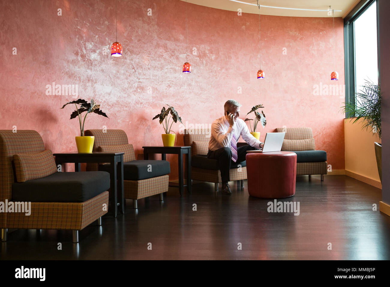 Caucasian man in an hip office lobby area - Stock Image