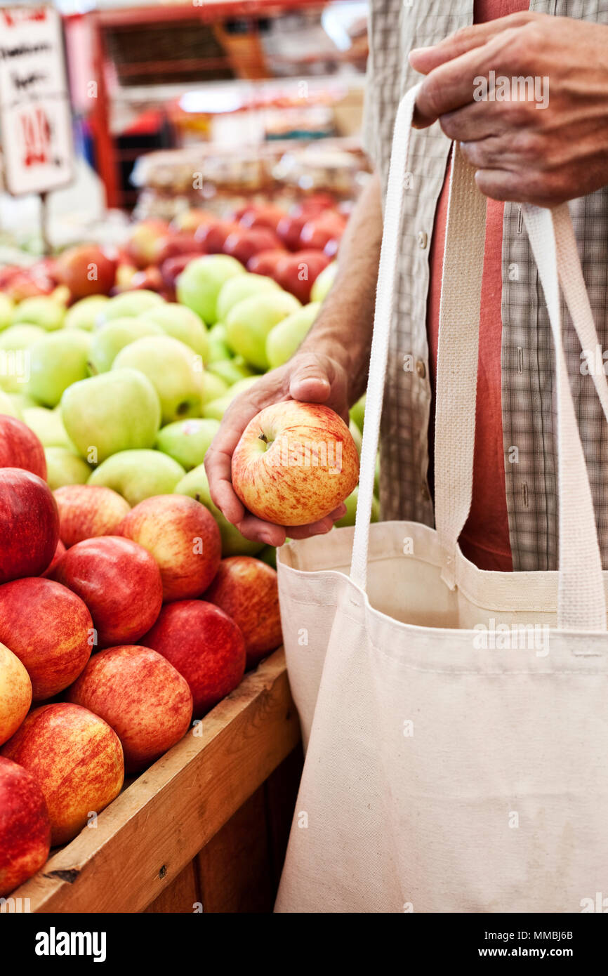 Close up of person holding shopping bag and red apple at a fruit and vegetable market. - Stock Image