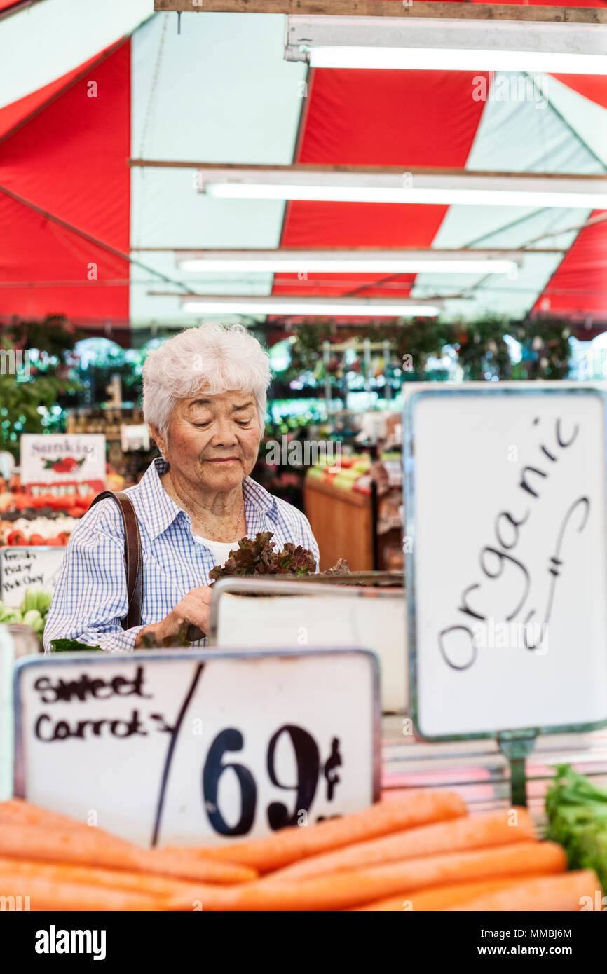 Senior woman standing at a stall in a fruit and vegetable market, looking at lettuce. - Stock Image