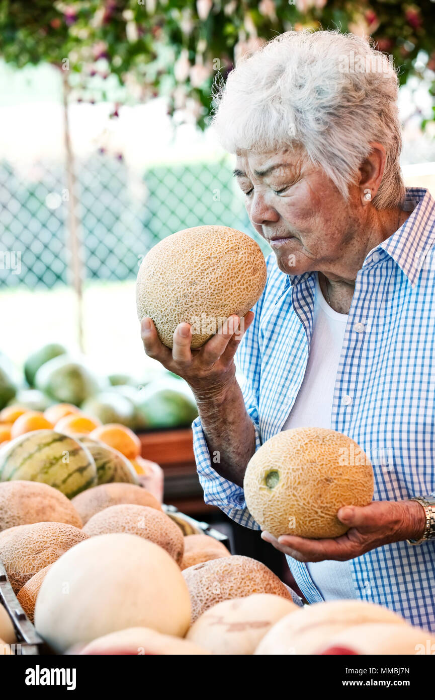 Senior woman standing at a farm stall, holding a fresh melon to her nose, smelling it. - Stock Image