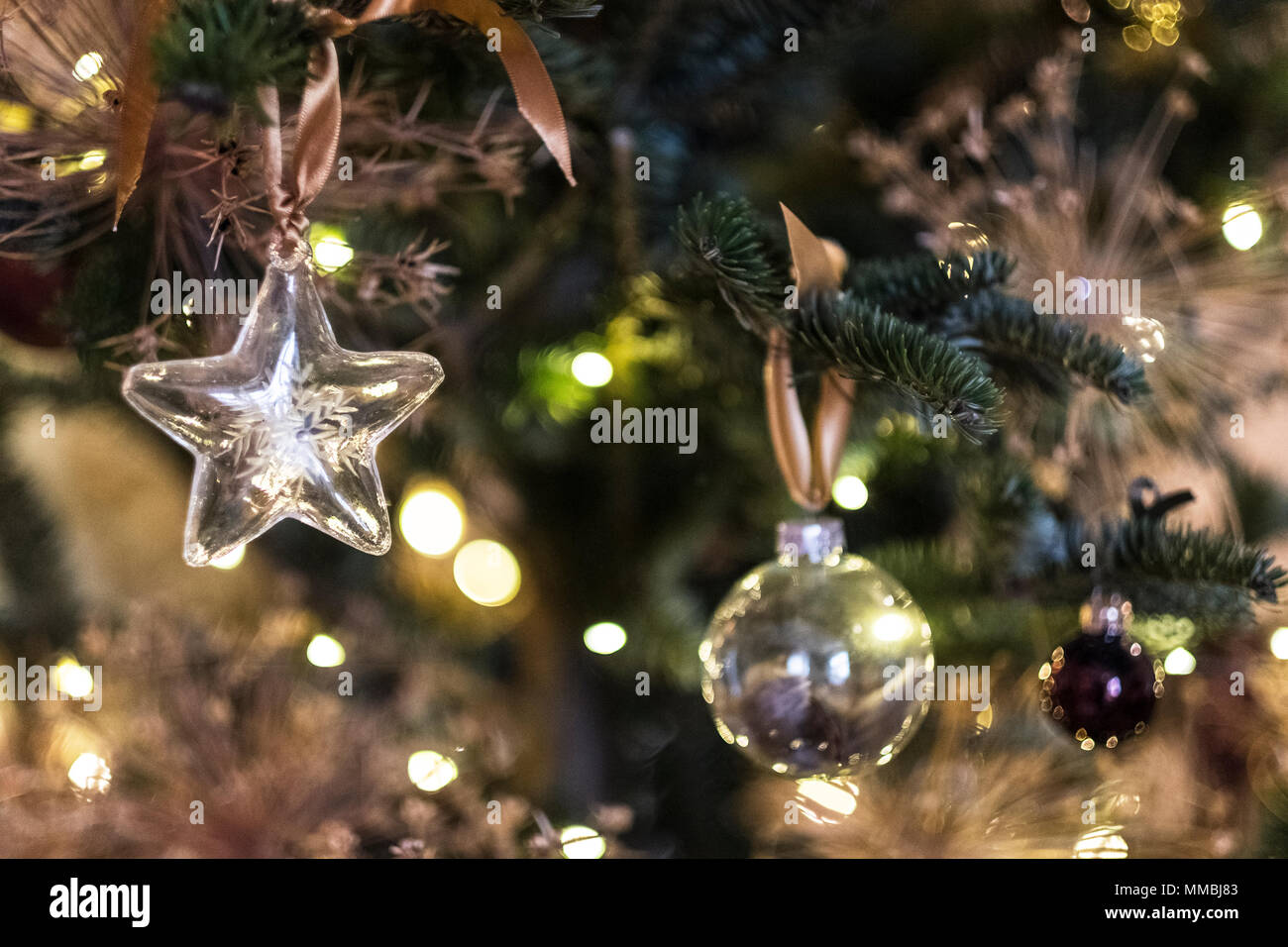 Close up of star shaped glass ornament and bauble on Christmas Tree. - Stock Image