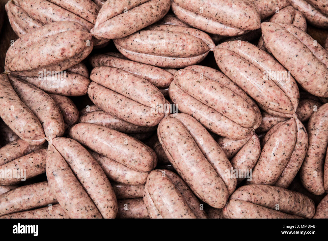 High angle close up of freshly made pork sausages at a butcher shop. - Stock Image