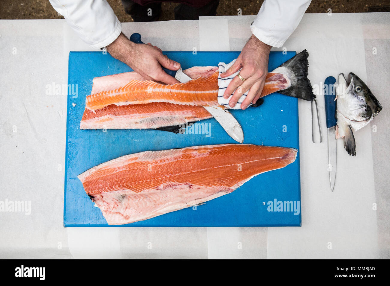 High angle close up of fishmonger standing at a table, cutting and filleting fresh salmon on blue chopping board. - Stock Image