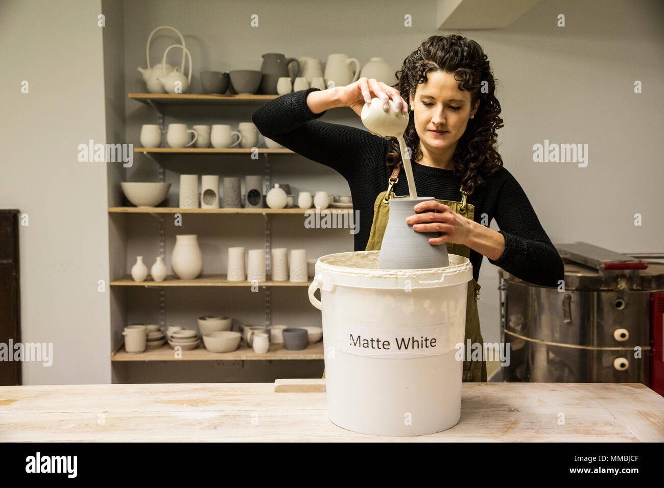 Woman with curly brown hair wearing apron standing in pottery workshop, pouring white glaze over unfired vase. - Stock Image