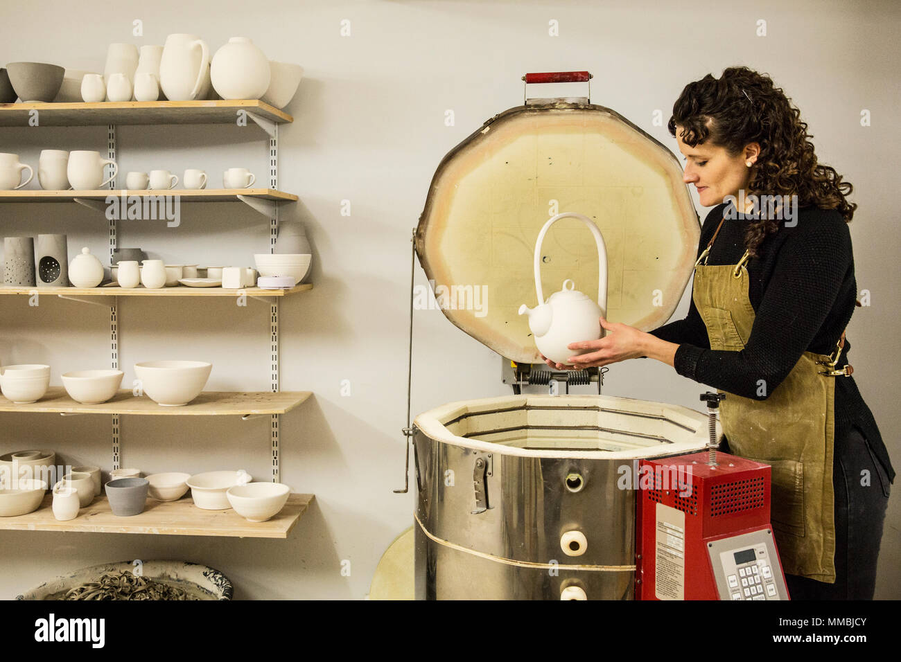 Woman with curly brown hair wearing apron standing in pottery workshop, placing vase into kiln. - Stock Image