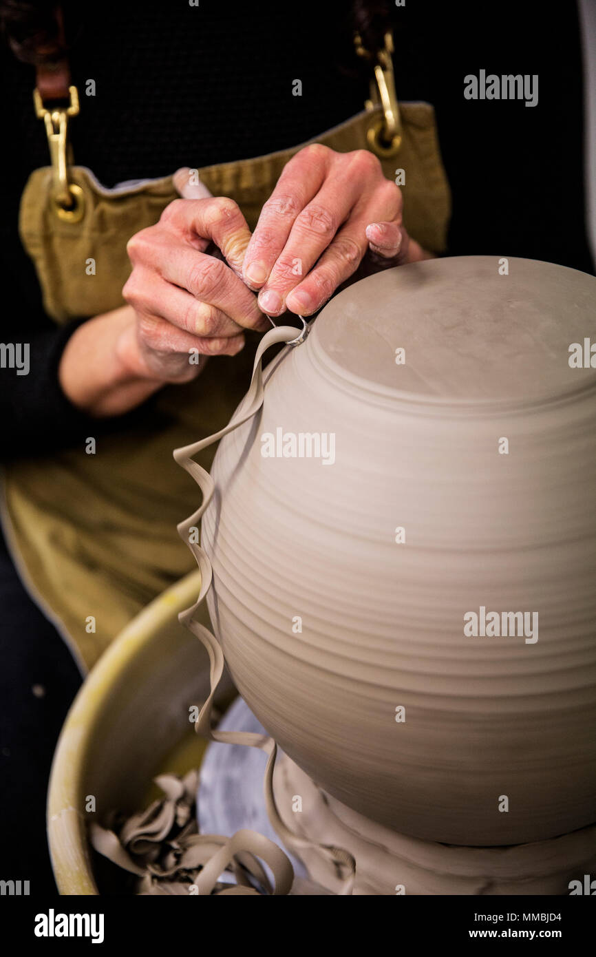 Close up of potter wearing apron working on spherical clay vase on pottery wheel. - Stock Image