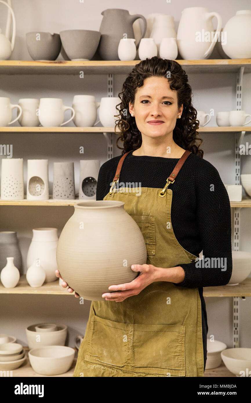 Woman with curly brown hair wearing apron holding unfired spherical clay vase. - Stock Image