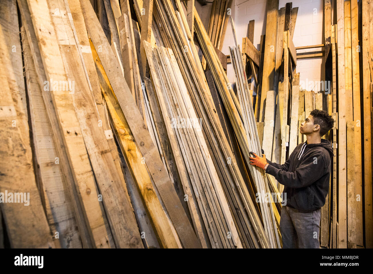 Young man wearing work gloves standing next to a stack of wooden planks in a warehouse. - Stock Image