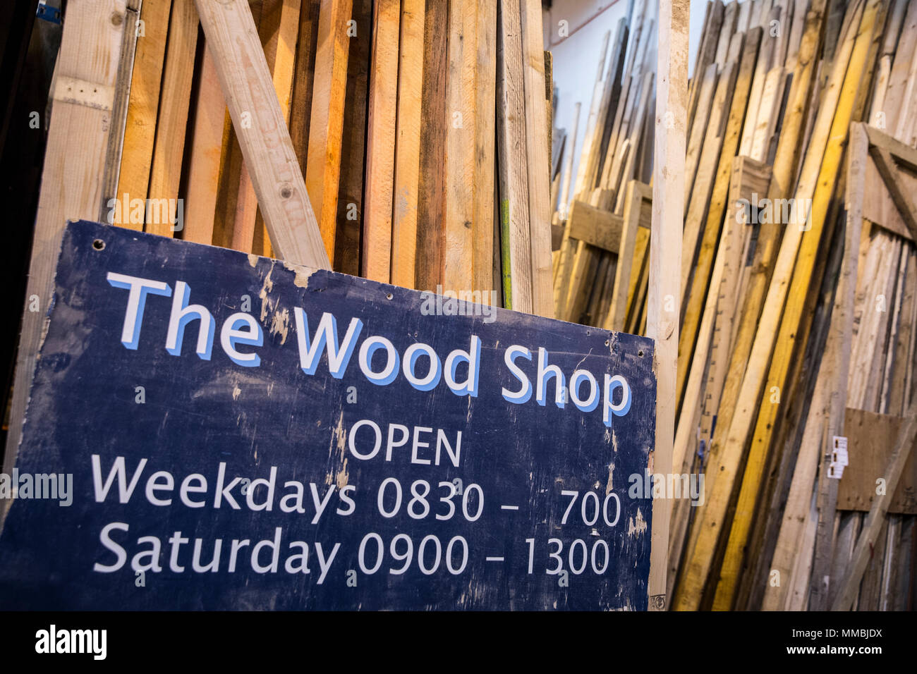 Close up of old blue Open sign for Wood Shop leaning against a stack of wooden planks. - Stock Image