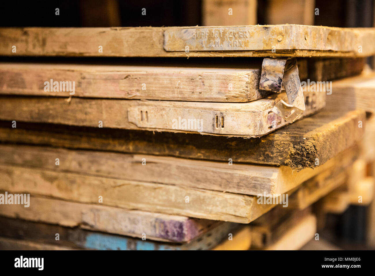 Close up of large selection of wooden planks stacked on shelves in a warehouse. - Stock Image
