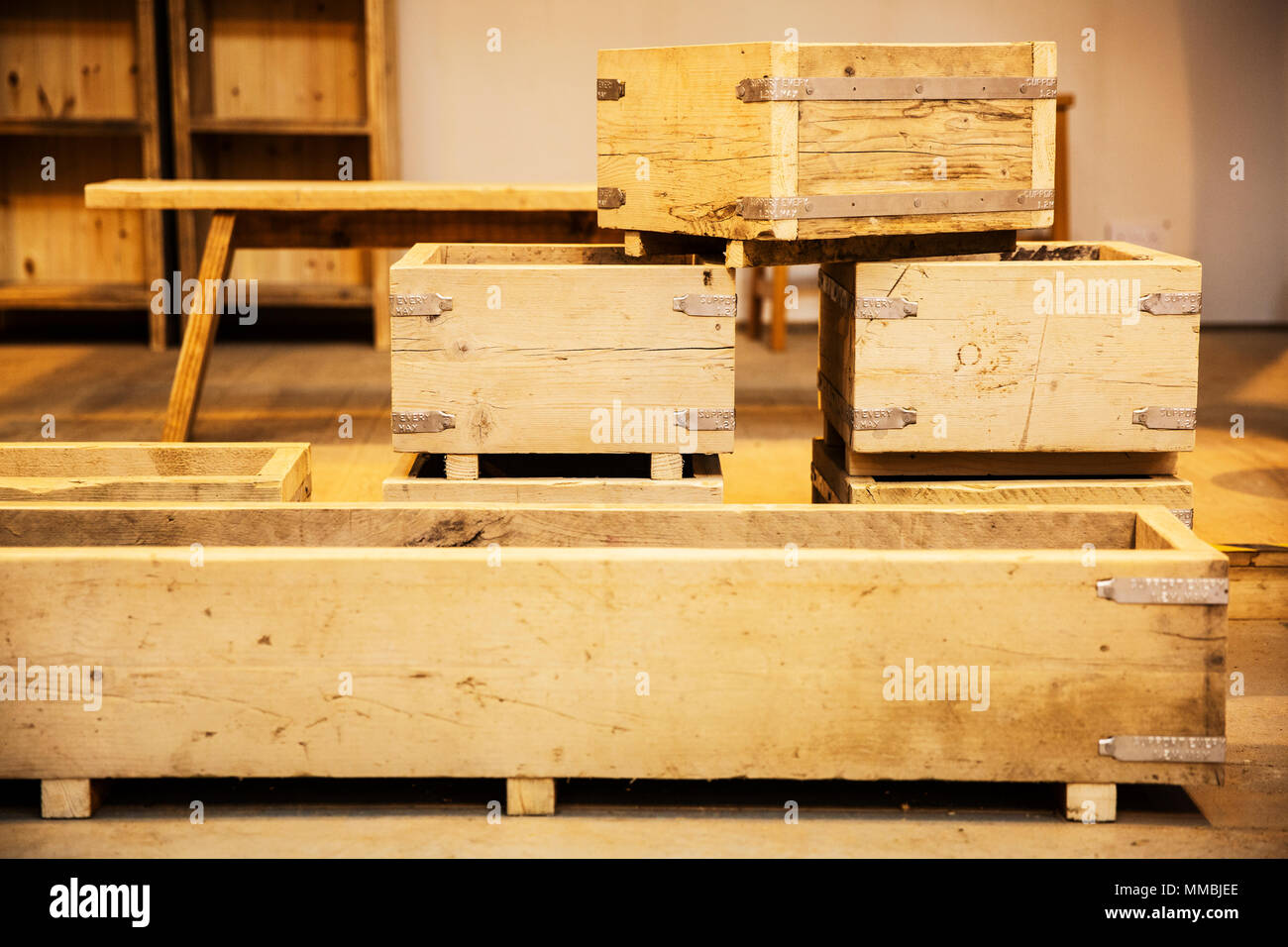 Stack of wooden crates in various sizes in a warehouse. - Stock Image