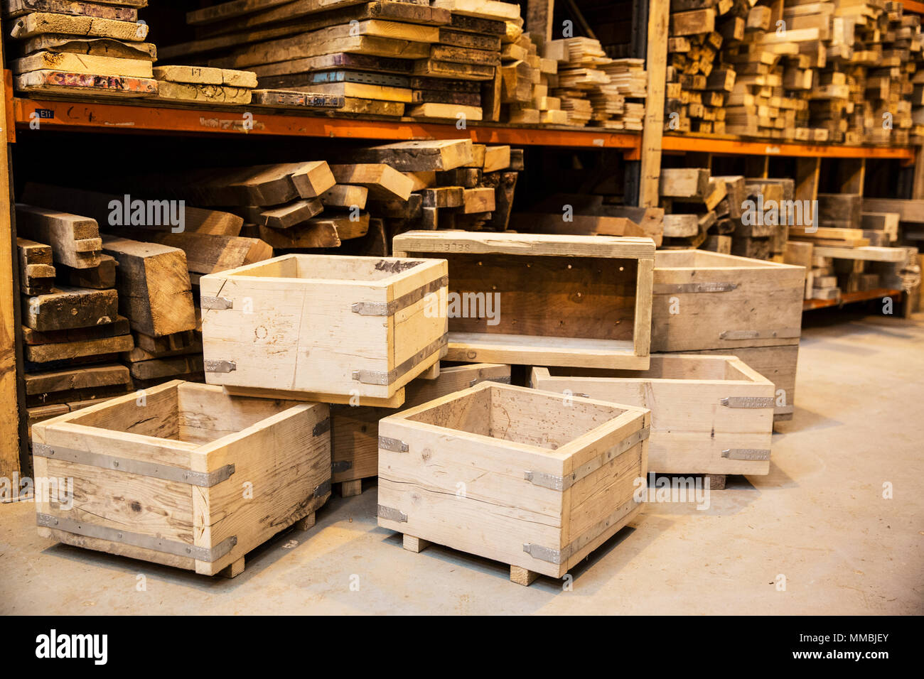 Shelves with wooden planks and a stack of wooden crates in a warehouse. - Stock Image