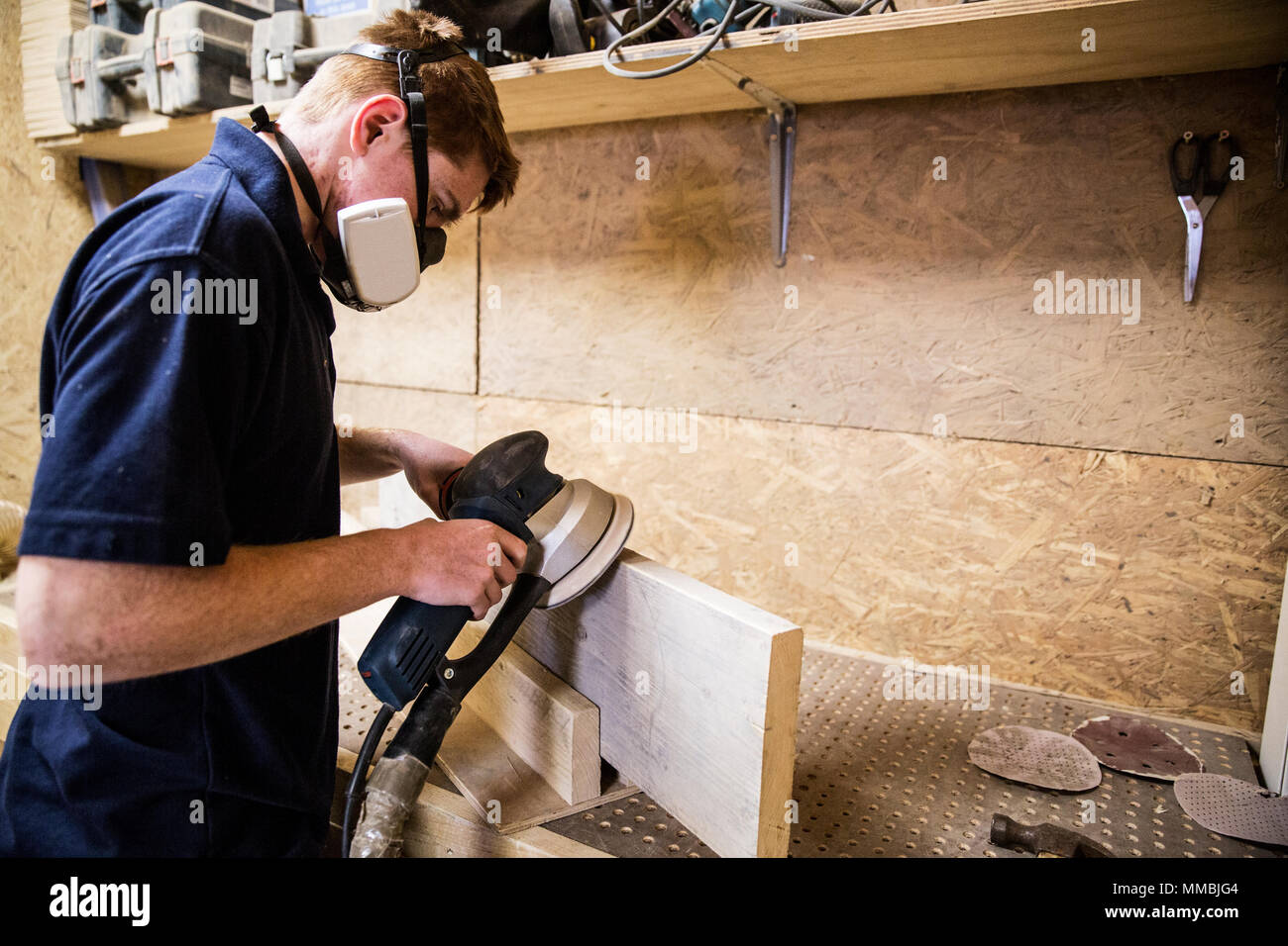 Young man wearing dust mask and protective goggles standing in a workshop, using sander to smoothen edge of piece of wood. - Stock Image