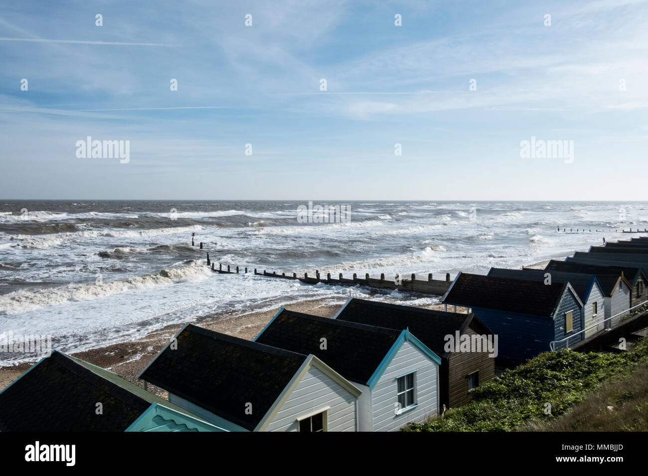 Seascape over a row of wooden beach huts, with waves rolling onto beach near groyne. - Stock Image