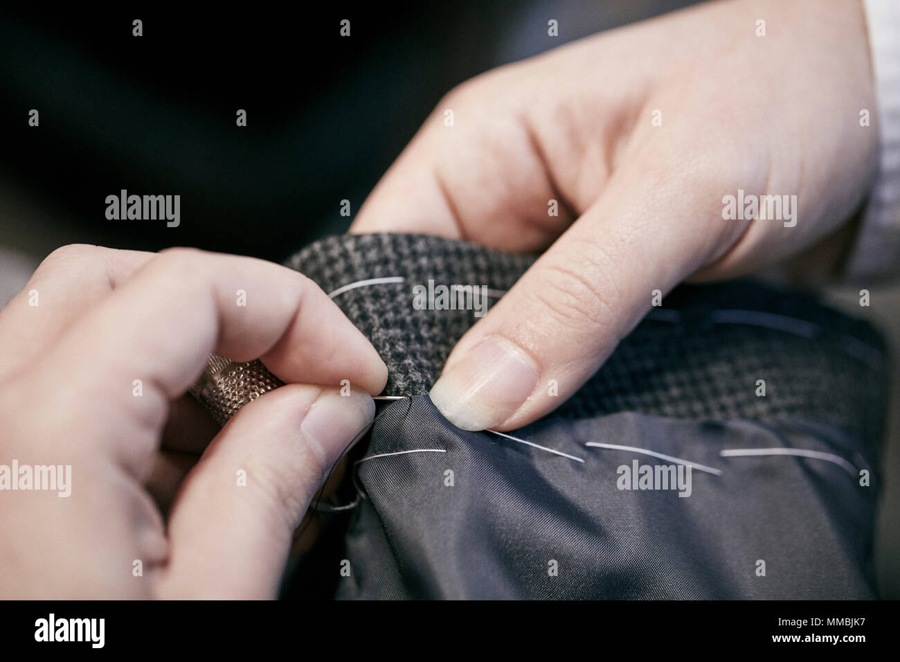 Sewing by hand using needle and thread - Stock Image