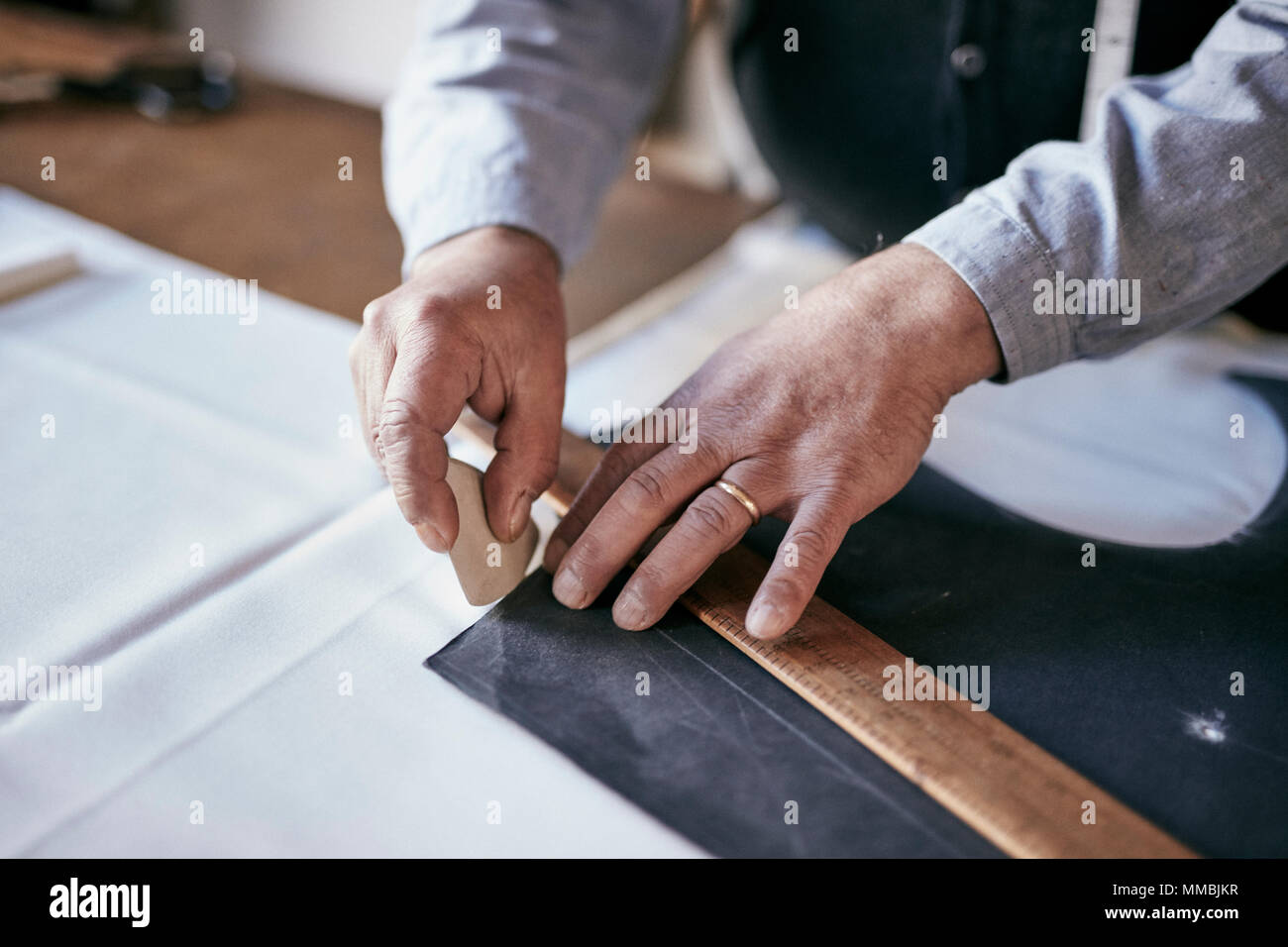 Tailor using chalk and ruler to outline pattern on fabric - Stock Image