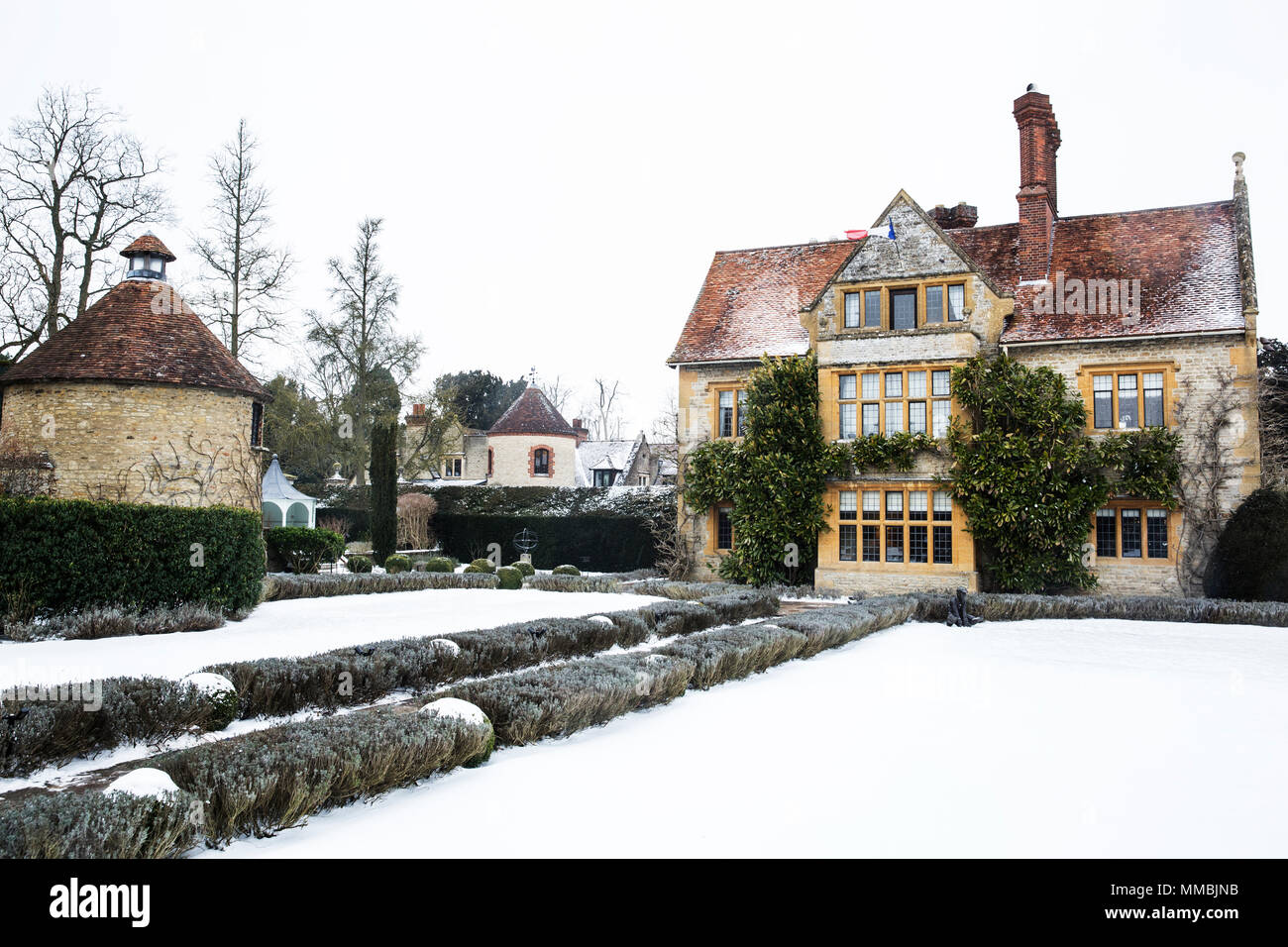 Historic 17th century manor house with tall chimneys, a hotel with snow covered grounds in winter. - Stock Image